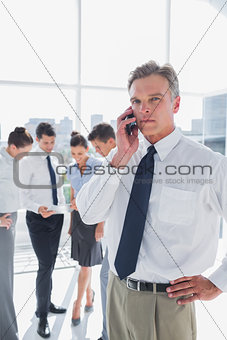 Serious boss on the phone standing in a modern office