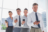 Team of business people standing together in line with their mobile