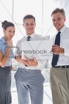 Three smiling business people using a laptop