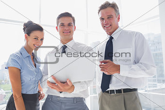 Three smiling business people holding a laptop