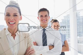 Smiling attractive businesswoman standing with arms crossed