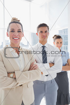 Smiling attractive businesswoman standing with arms folded
