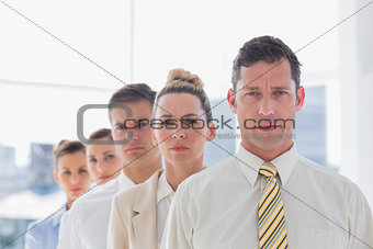 Serious handsome businessman standing with team