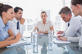 Businesswoman looking at camera with colleagues working around