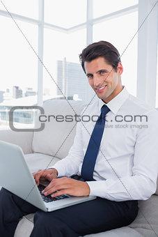 Smiling business man using laptop