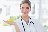 Attractive woman doctor showing an apple