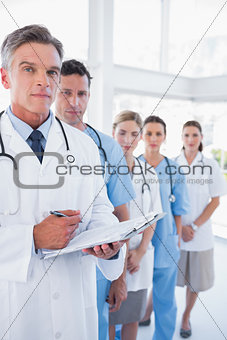 Serious doctor holding clipboard and standing in front of his medical team