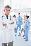 Doctor with arms folded in front of his medical team