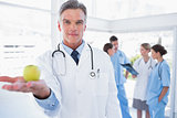 Doctor presenting an apple in his hand