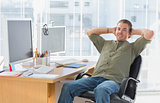 Smiling designer leaning back at his desk