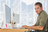 Smiling creative business employee working on computer