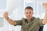 Creative business employee raising his arms