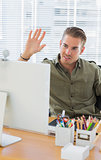 Creative business employee waving in a modern office