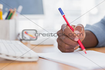 Man drawing with a red pencil on a desk