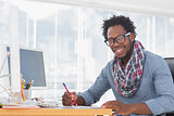 Smiling designer drawing with a red pencil on a desk