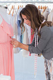 Fashion designer adjusting dress