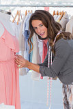 Fashion designer picking needles in a dress
