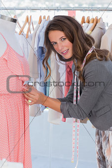 Fashion designer picking needles in a dress
