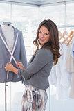 Attractive fashion designer measuring blazer lapel