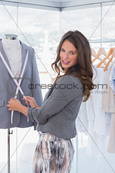 Attractive fashion designer measuring blazer lapel
