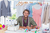 Smiling fashion designer sitting behind a desk