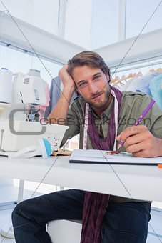Attractive fashion designer working at his desk