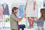 Fashion designers adjusting dress