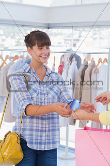 Cashier giving shopping bag and credit card