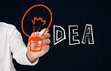 Businessman drawing orange light bulb as the i in idea