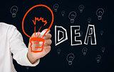 Businessman drawing big orange light bulb as the i in idea