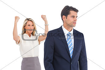 Businessman and a serious businesswoman with raised arms