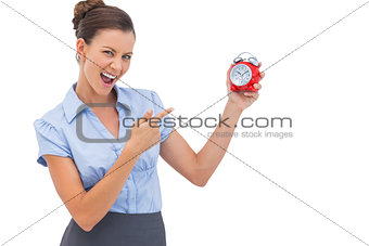 Businesswoman pointing at alarm clock