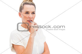 Focused businesswoman with pen on mouth