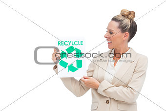 Businesswoman looking at recycling logo on paper