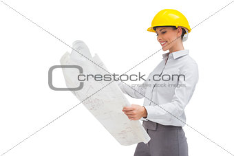 Architect reading a plan with yellow helmet
