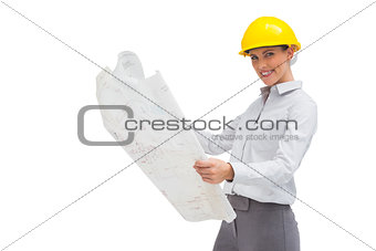 Architect reading blueprint with yellow helmet