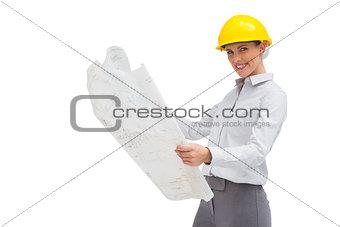 Architect reading blueprint with yellow helmet