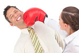 Businesswoman punching businessman with boxing gloves
