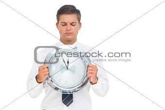 Businessman holding and looking at clock