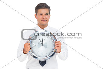 Anxious businessman holding a clock