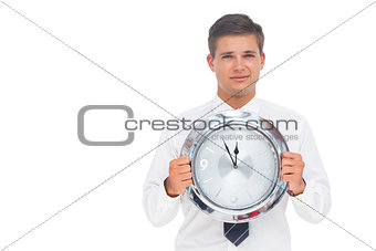 Nervous businessman holding a clock