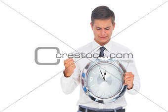 Nervous businessman holding and looking at clock