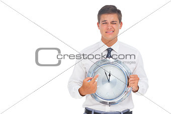 Worried businessman holding and pointing at clock