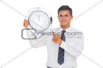 Businessman holding and showing a clock