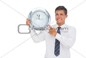Anxious businessman holding and showing a clock