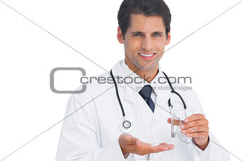 Happy doctor smiling and holding tablets and water
