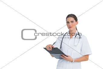 Nurse holding clipboard and looking at camera with large copy space