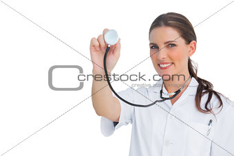 Happy nurse holding up stethoscope