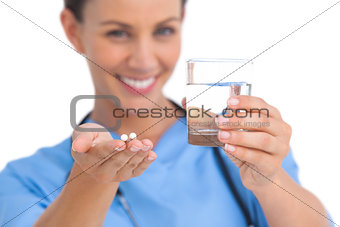 Smiling surgeon holding medicine and glass of water