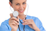 Smiling surgeon holding up stethoscope
